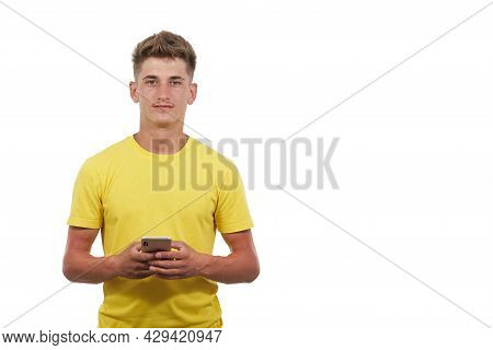 Portrait Of Handsome Man Dressed Casual In Yellow T-shirt. Using The Smart Phone