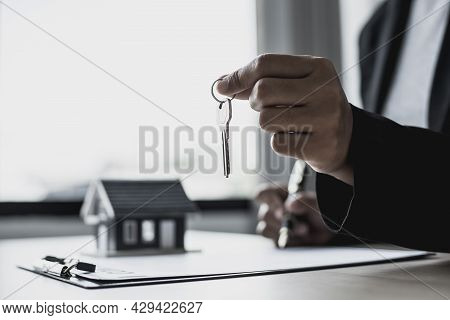 The Salesperson Holds The Keys To Hand To The Customer On The Day Of Handover Of The House In The Ho