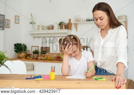 Young Girl Doing Homework During Extra-curricular Classes With A Tutor. Frustrated Young Mother Or T
