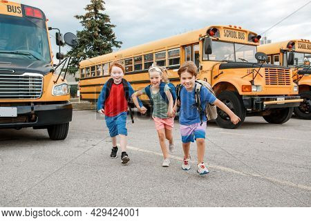 Happy Caucasian Children Boys And Girl Kids Students Running Near Yellow School Bus. Education And B