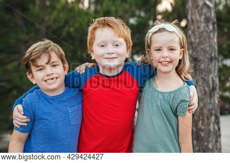 Three Happy Caucasian Little Children Kids Boys And Girl Hugging Together Outdoor In Park. Group Of
