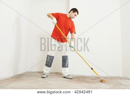 Parquet worker with paint roller making floor prime coating  at home repair renovation work