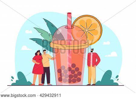 Tiny People Standing Next To Huge Glass Of Bubble Tea. Orange Boba Milk Tea In Takeaway Plastic Cup
