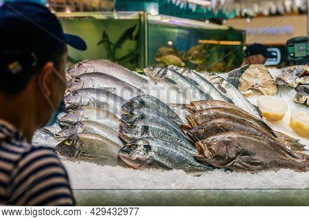 Fresh Fish On Ice. Unrecognizable Seller Back To Us With Seafood At Seafood Market. Sale Of Fresh Fi