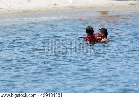 New Orleans, La - August 1: Man Swimming With Son In Lake Pontchartrain On August 1, 2021 In New Orl