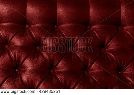 Red Leather Upholstery On The Sofa With Light And Shadow, Close-up.
