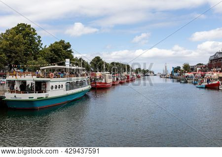 Rostock, Germany - July 20, 2021: Excursion boats and fishing boats at Alter Strom harbor of Warnemünde district at the Baltic Sea coast.
