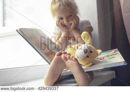 Cute Little Caucasian Child Sits Near Window And Reads Book, Funny Expression, Barefoot In Focus, Ki