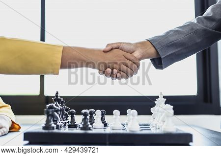 Two Business Women Shake Hands After Playing A Game Of Chess, Playing A Game Of Chess Is Like Planni