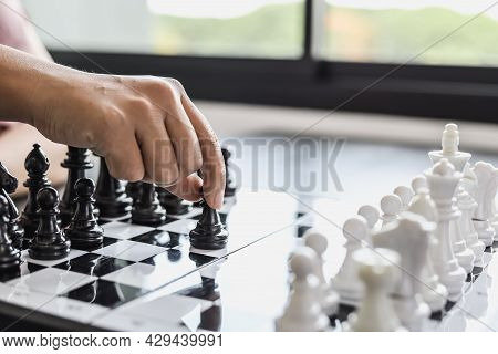 A Businesswoman Holding A Black Chess Piece Walks Forward On A Chessboard, Comparing The Chessboard
