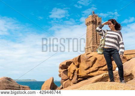A Young Woman At The Mean Ruz Lighthouse, Port Of Ploumanach, In The Town Of Perros-guirec In The Co