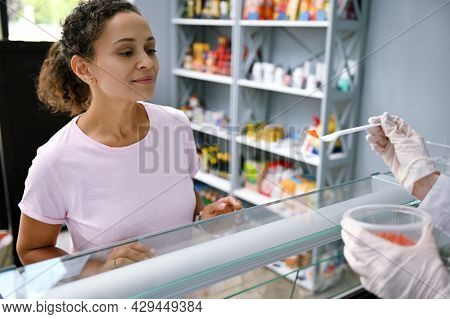 Cropped Fishmonger Standing Behind The Counter, Holding A Jar With Red Salmon Caviar And Serving The