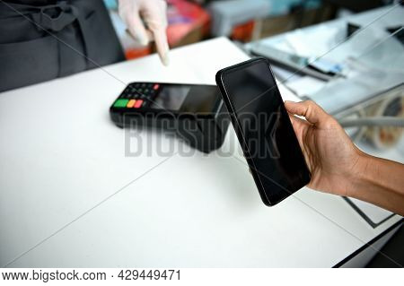 Customer With Smartphone Paying In Seafood Store, Contactless Payment Concept. Paying Bill Through S