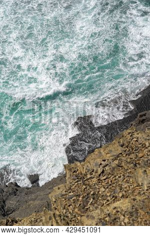 Aerial View Of The Ocean Waves And Cliff. Blue Water Background. Sea Top View. Atlantic Ocean Beach
