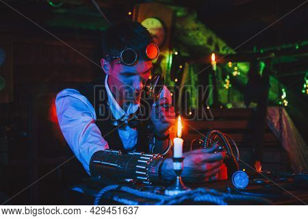 Male Inventor In A Steampunk Suit Repairs A Fantastic Mechanism At A Table