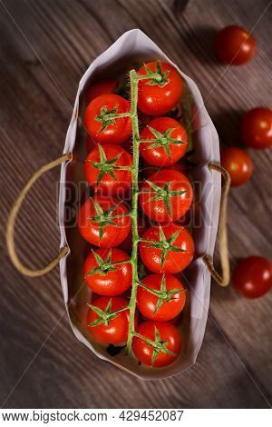Top View Of Trusses Of Small Ripe Cherry Tomatoes In Bag On Wooden Background