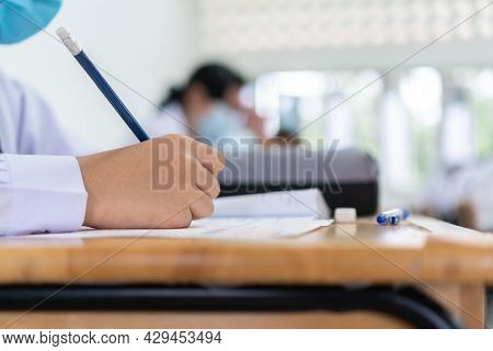 Hands Of Asian Students Group Learning And Concentrate Writing Test In Exam Room Wear Facemask Preve