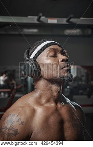 Athletic African American Man In Wireless Headphones With Closed Eyes And Naked Shoulders During Tra