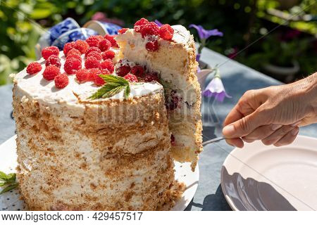 A Piece Of Homemade Raspberry Sponge Cake On A Table In The Garden On A Bright Sunny Morning. Nearby