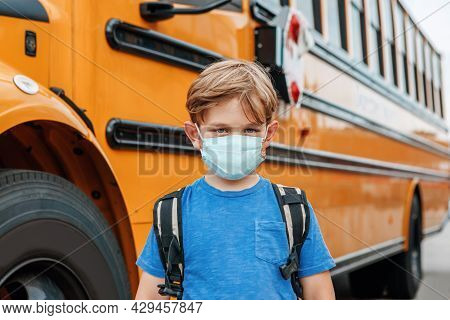 Boy Kid Student In Protective Face Mask Near School Yellow Bus Outdoors. New Normal At Coronavirus C