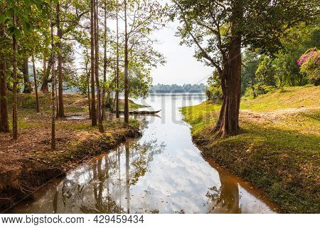 Traditional Long Tail Wooden Boat In A Small Lake Near Siem Reap, Cambodia. The Sky And The Trees Ar