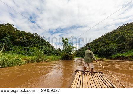 Men On A Wooden Or Bamboo Raft On The Mae Taeng River Near Chiang Mai, Thailand. The Thai Men Steer