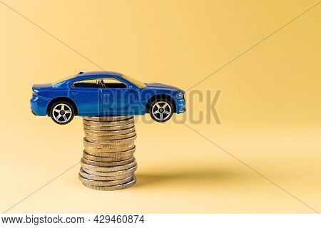 Varna, Bulgaria, July 15, 2021. Blue Toy Car On The Top Of Coin Stack On A Yellow Background. Car In