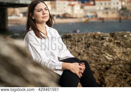 Beautiful Young Brunette Woman Sits On Stone Pier And Gazes Thoughtfully Out To Sea, Beautiful Mount