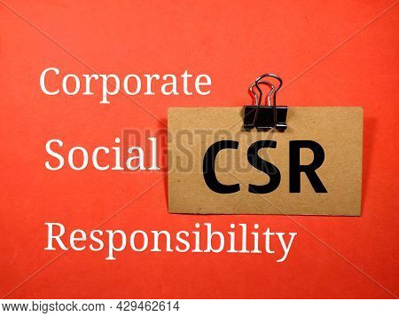 Business Concept.text Csr (corporate Social Responsibility) Writing On Brown Card On A Red Backgroun