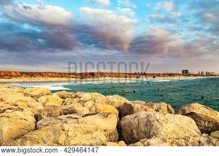 Evening twilight on the Mediterranean Sea. Walk along the breakwater that protects the yacht harbor from storms. Herzliya, Israel.