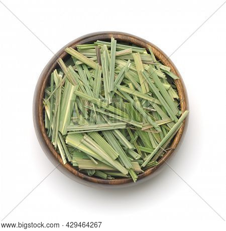 Top view of dried lemongrass herb in wooden bowl isolated on white