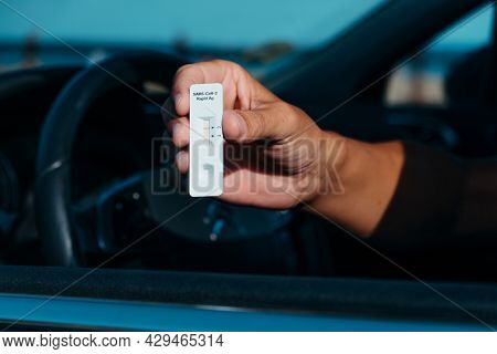a young caucasian man, sitting in the driver seat of his car, shows a covid-19 test device with a negative result