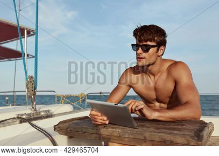 Young man sitting and using digital tablet of his yacht in sea or ocean. Luxury boat. Beautiful naked guy wear glasses. Concept of sailing vacation or tourism. Summertime. Sunny daytime