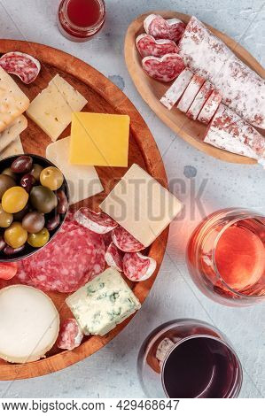 Cheese Board And Charcuterie Platter With Wine And Olives, Top Shot. Red And Rose Wine, Fuet, Salami
