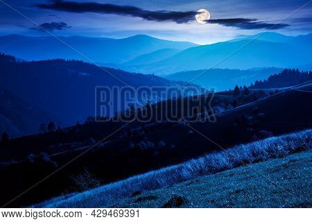 Mountainous Countryside Landscape At Night. Grassy Meadows And Trees On Hills Rolling In To The Dist