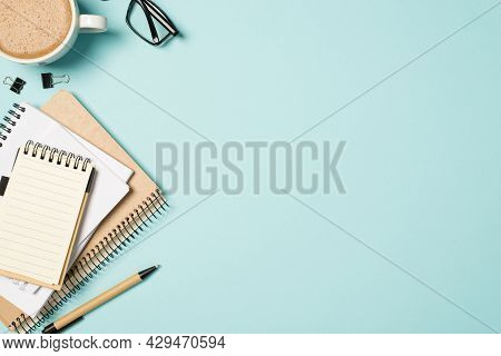 Top View Photo Of Glasses Cup Of Frothy Coffee Binder Clips Pen And Stack Of Planners On Isolated Pa