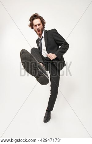 Full length portrait of a handsome well-groomed man fashion model who steps on the camera with aggression and shouts. Fashion concept. Emotions. White background.