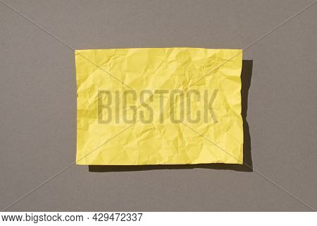 Overhead Photo Of Crumbled Yellow Paper In The Middle Isolated On The Grey Backdrop