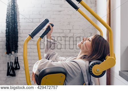 Bored Lazy Sportive Woman Trying Training On Fitness Machine In Gym