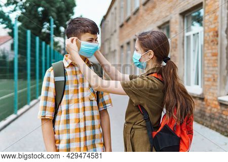 schoolboy and schoolgirl posing on the way to school, wearing a protective mask on their faces from a coronavirus infection, education and back to school concept