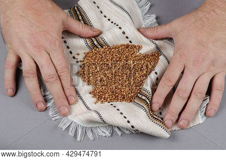 Dried Brown Uncooked Buckwheat Grains Lie On A White Ethnic Fringed Towel. Portion Of Buckwheat Groa