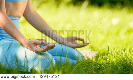 Yoga practitioner lady in blue tracksuit holds hands on knees joining thumbs