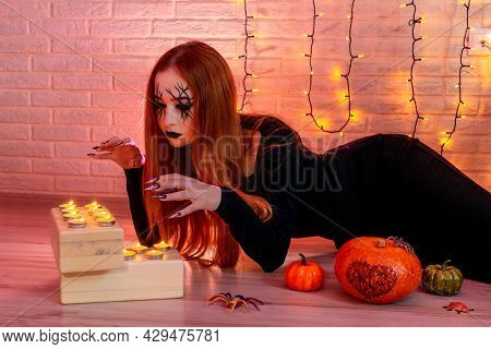 Halloween Witch Near Candles, Garland On Background.