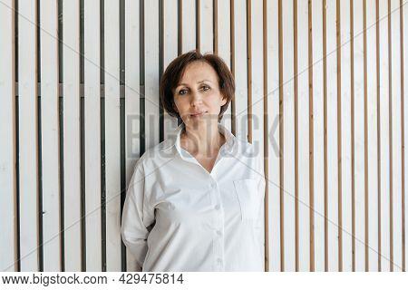 Senior Businesswoman Portrait On White Wooden Background.