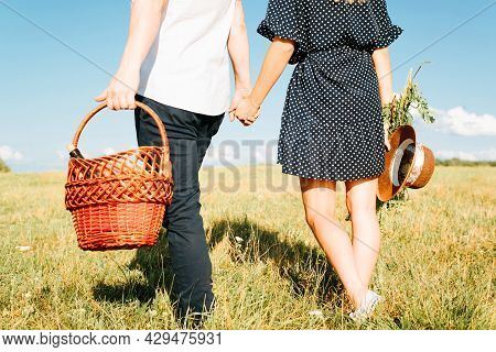 Family Picnic In Nature. Back View Of Beautiful Young Couple Hold Hands In Field, Basket With Bottle