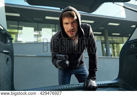 Angry european robber looking in car trunk. View from auto trunk with human victim. Male bearded bandit wear black hoodie with gloves and hold pistol. Concept of kidnapping. City daytime