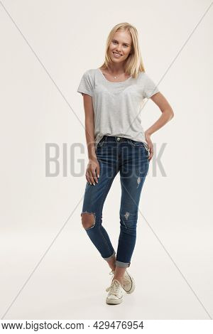 Front view of young smiling european girl looking at camera. Beautiful blonde female teenager with blue eyes wear white t-shirt and jeans. Isolated on white background. Studio shoot. Copy space