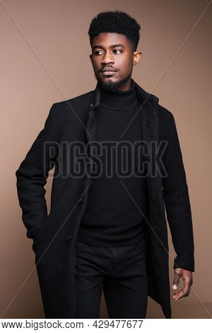 Close-up Of African Elegant Man In Black Jacket Posing At Camera Isolated On Beige Background