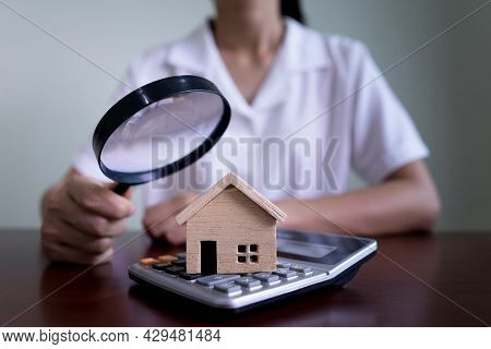 Woman Using A Magnifying Glass To House Model And Calculator. Searching Housing And Home Insurance C