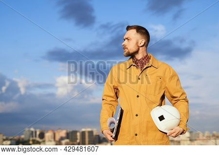 Construction Foreman, Supervisor, Engineer Or Building Contractor. Male In Orange Jacket Standing An